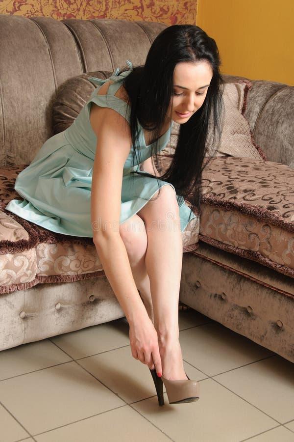 妇女投入穿上鞋子坐长沙发 免版税库存照片