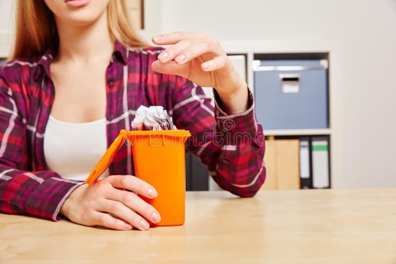 妇女投掷纸入一个小垃圾箱 免版税库存照片