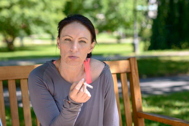 妇女抽烟的香烟,当坐长凳时 库存图片