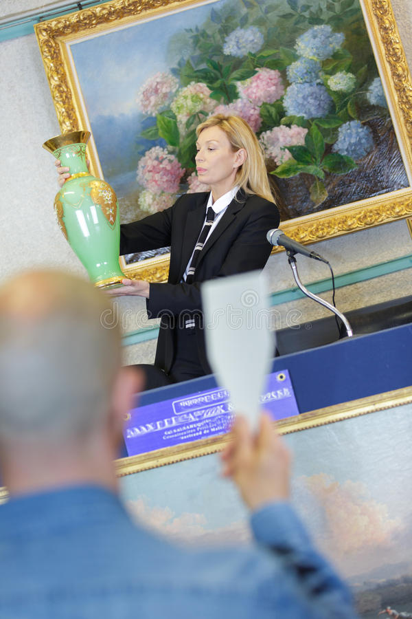 妇女拍卖人和人谈判的价格项目 免版税库存图片