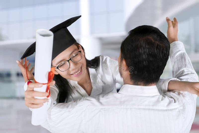妇女拥抱她的男朋友毕业典礼举行日 库存照片