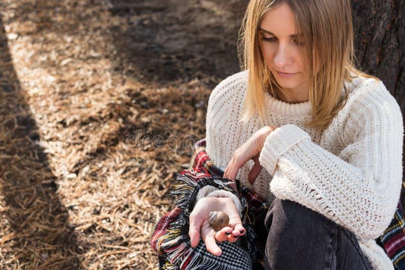 妇女拿着一只蜗牛 免版税库存照片