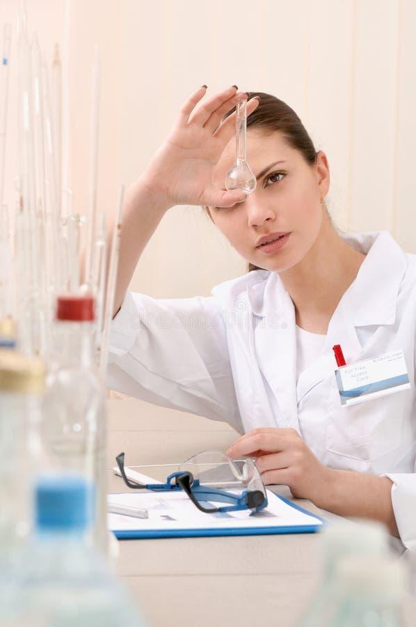 妇女拿着一块空的试管和手表严密地对此的实验员 库存图片