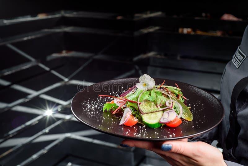 妇女拿着一块黑暗的板材用蕃茄、黄瓜、葱、菠菜和芝麻菜新鲜蔬菜沙拉  库存图片