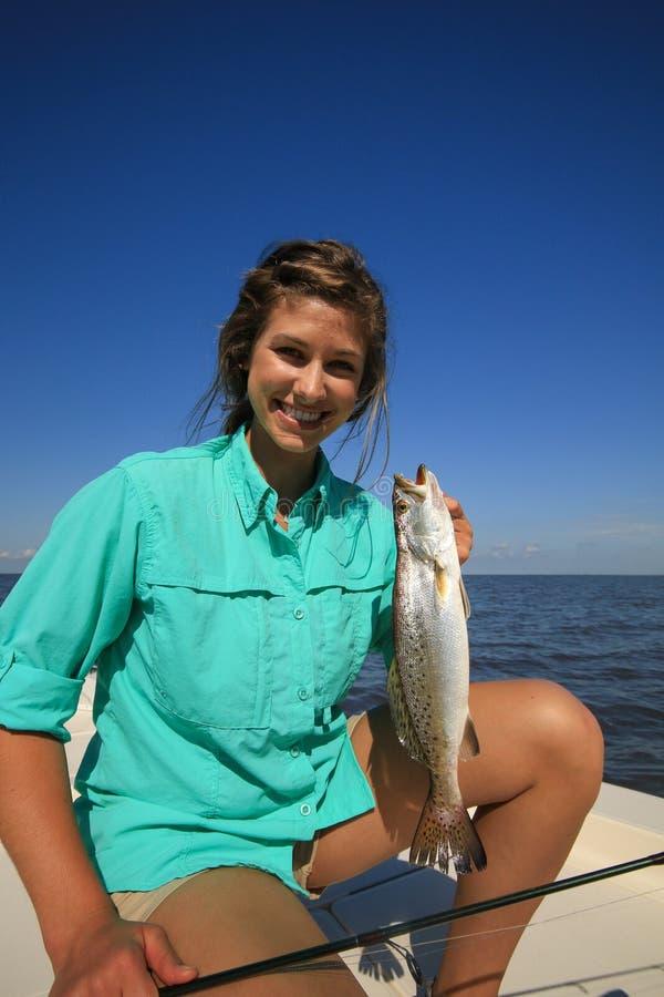 妇女拿着一条有斑点的鳟鱼的盐水钓鱼在路易斯安那 库存图片