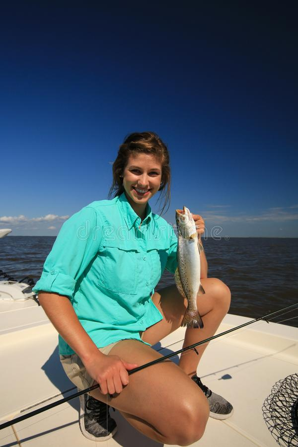 妇女拿着一条有斑点的鳟鱼的盐水钓鱼在路易斯安那 免版税库存照片