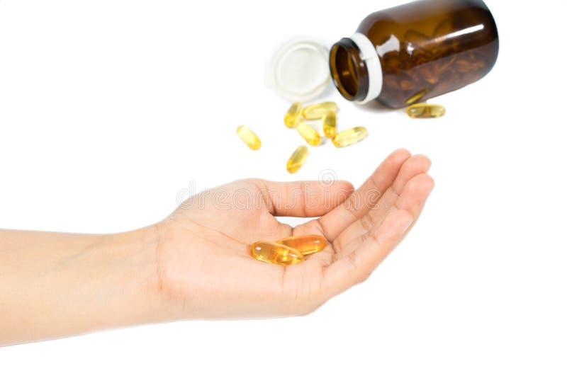 妇女拿着与Ω 3和维生素D健康饮食概念的` s手鱼油胶囊, 库存图片
