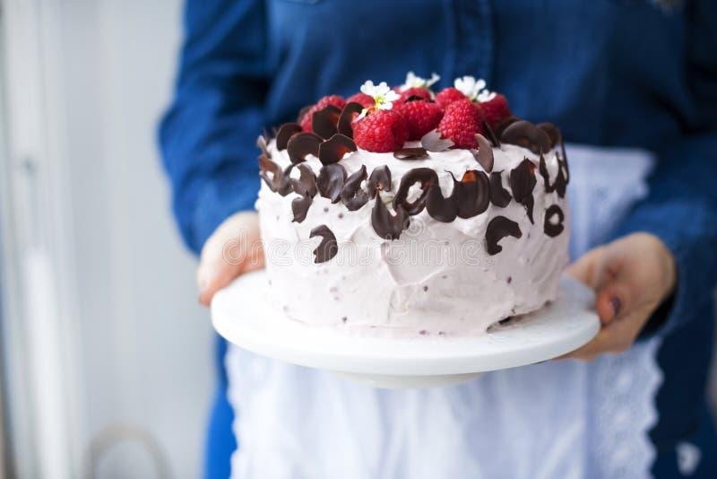 妇女拿着与桃红色奶油和新鲜的莓莓果的一个美丽的蛋糕,装饰用巧克力 卡路里食物 自由 库存照片
