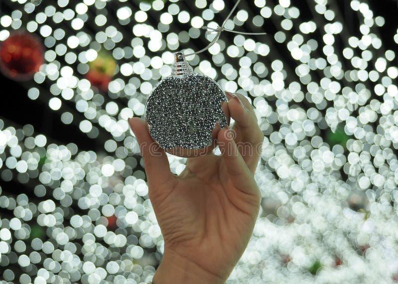 妇女拿着与bokeh光背景的` s手银色chritmas球 免版税库存图片