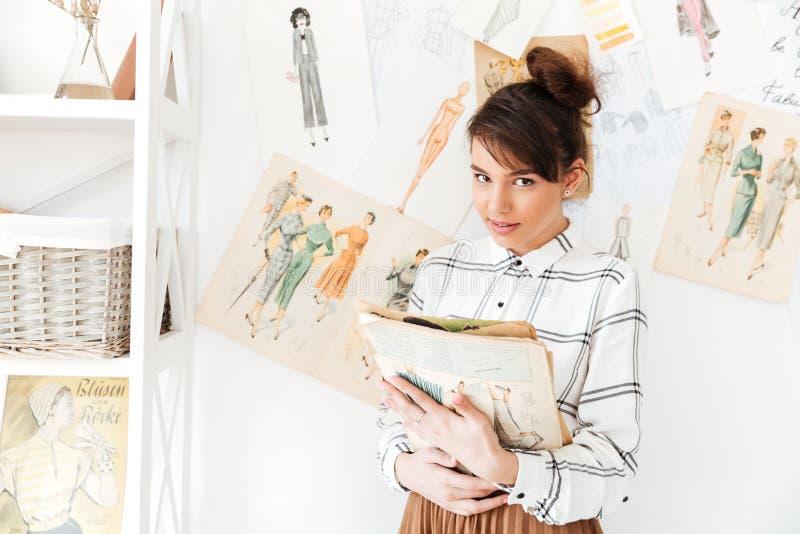 妇女拿着写生簿的时装设计师,当站立在她的演播室时 库存照片
