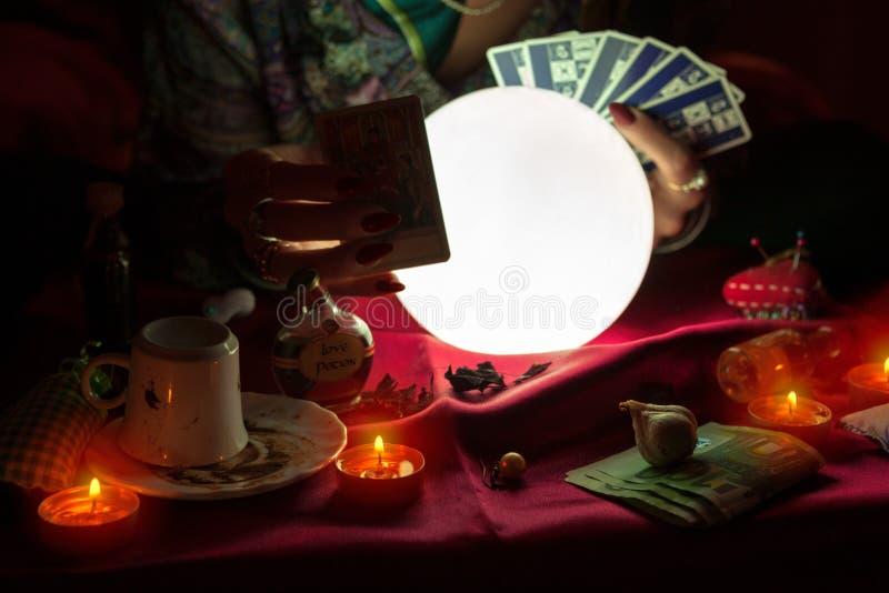 妇女拿着占卜用的纸牌的算命者 免版税库存图片