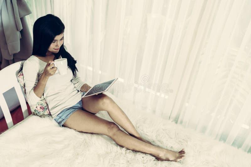 妇女拿着咖啡杯和坐在一张床上的一种片剂在a 免版税库存图片