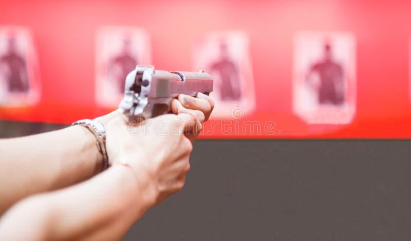 妇女拿着大酒瓶枪,在触发器,瞄准的食指的两只手准备好射击在红色墙壁背景的目标 体育, 免版税库存照片