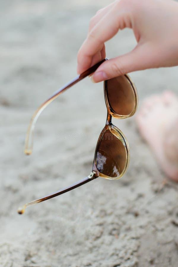 妇女拿着太阳镜的` s手照片反对沙子eyewear玻璃镜片夏天太阳辅助部件手穿戴秀丽时尚 免版税库存图片