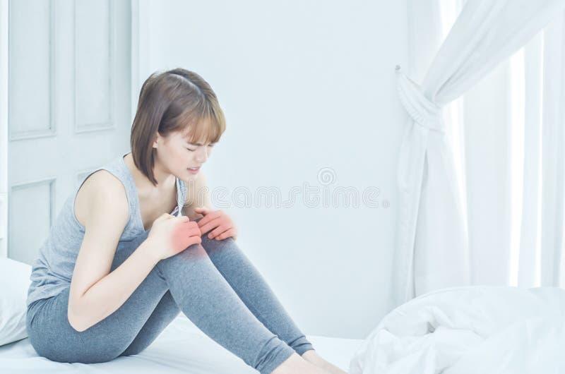妇女拿着她的膝盖 她有膝盖痛苦 库存图片