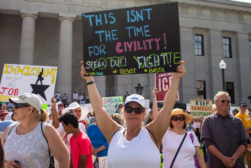妇女拿着抗议标志在移民集会 库存图片