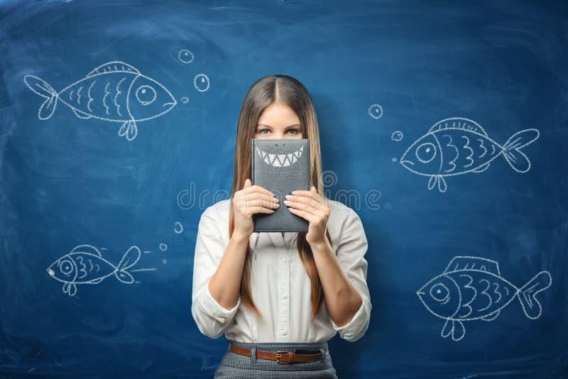 妇女拿着有拉长的鲨鱼牙的一个笔记本在与拉长的鱼的蓝色黑板背景 库存图片
