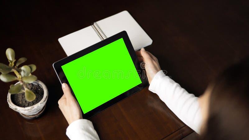 妇女拿着有绿色屏幕的片剂个人计算机 免版税库存照片