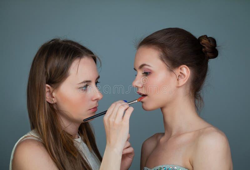 妇女拿着构成刷子和应用在完善的时装模特儿嘴唇的化妆师唇膏 库存照片