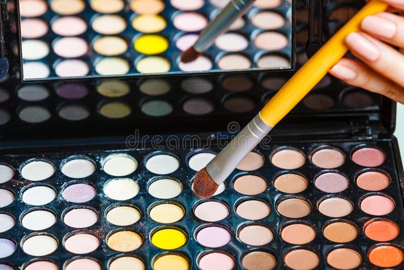 妇女拿着构成眼影调色板和刷子 免版税库存照片