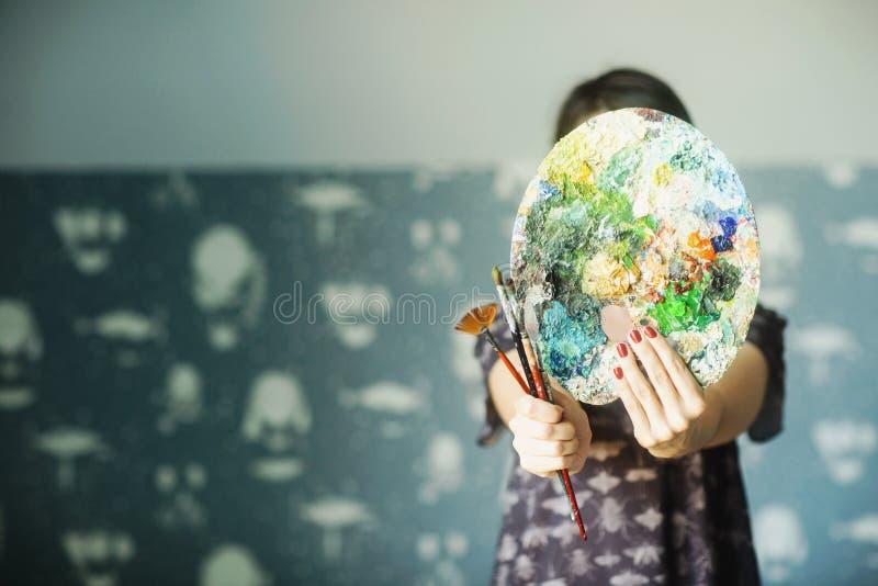 妇女拿着油漆和刷子调色板在她前面 r 库存图片