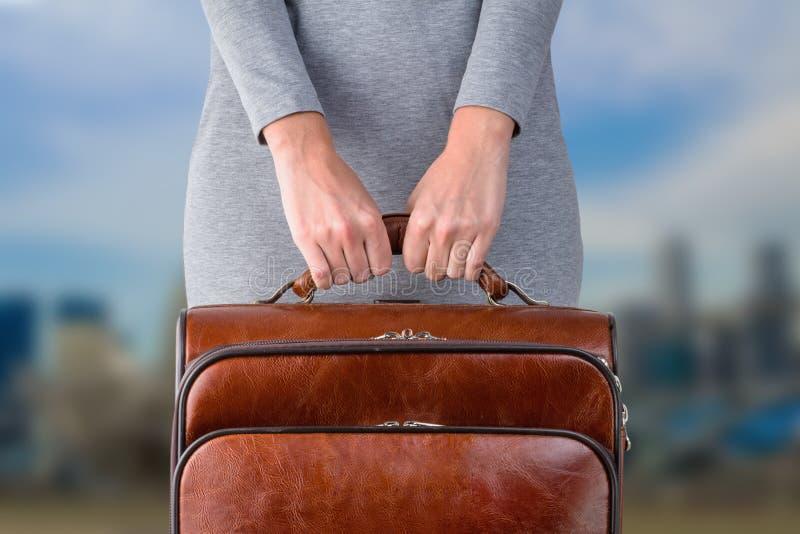 妇女拿着皮革手提箱 免版税库存照片