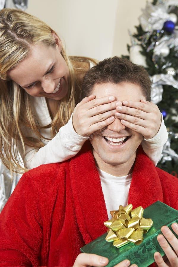 妇女拿着礼物的人的覆盖物眼睛 免版税库存图片