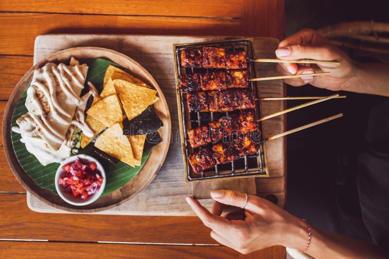 妇女拿着素食主义者坦佩烤串  免版税图库摄影