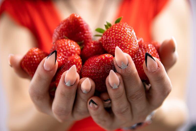妇女拿着草莓 免版税库存照片