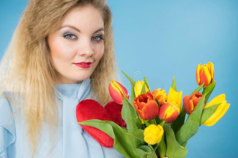 妇女拿着郁金香和红心 免版税库存图片