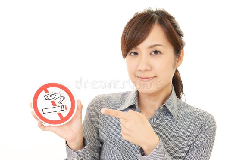 妇女拿着非抽烟的标志 免版税库存图片