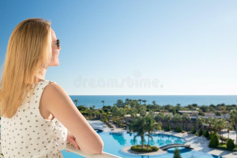 妇女指向与她的手指从一balkony的海在暑假 免版税库存图片