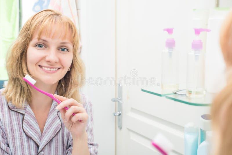 妇女掠过的牙在卫生间里 免版税库存图片
