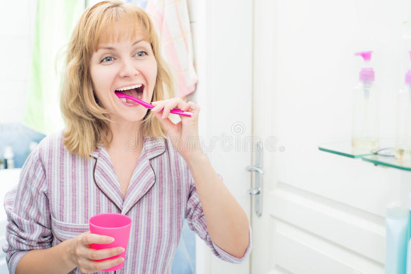 妇女掠过的牙在卫生间里 免版税图库摄影