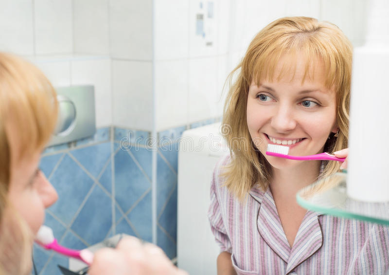 妇女掠过的牙在卫生间里 库存照片