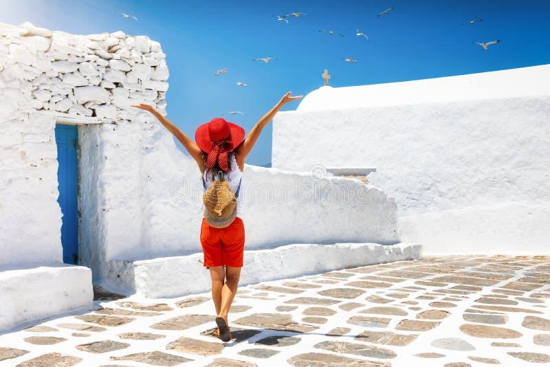 妇女探索希腊的基克拉泽斯海岛的白色胡同 免版税库存图片