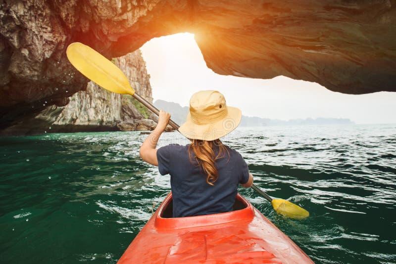 妇女探索皮船的下龙湾 免版税库存图片
