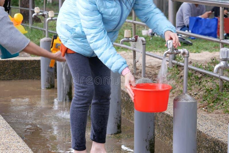 妇女接受雨水的行动到洗涤的手的一个罐里在公园 免版税库存照片