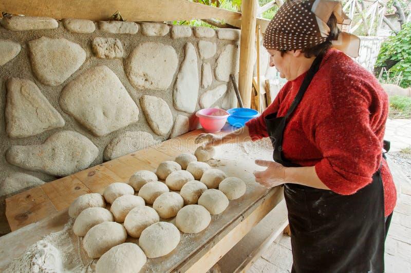 妇女揉的面团和烹调面包在农村房子厨房 库存照片