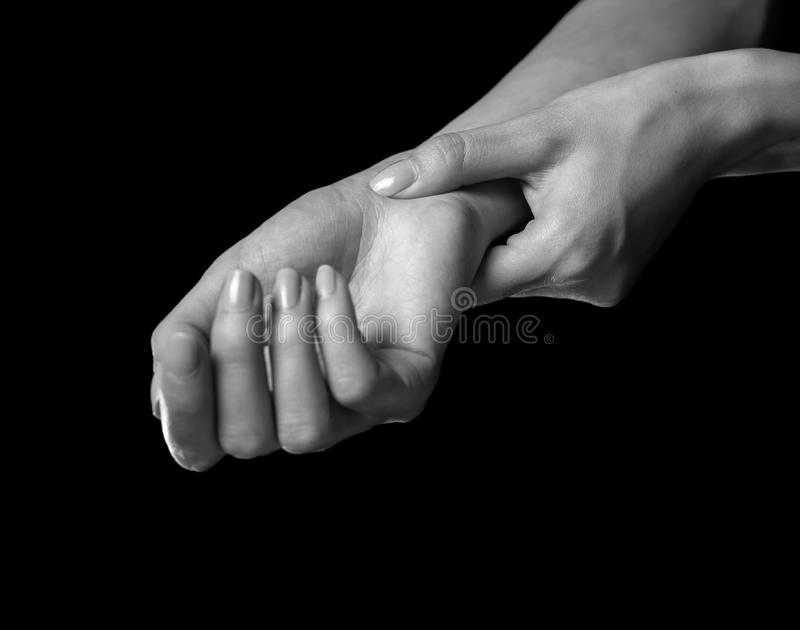 妇女握她的腕子,腕骨综合症状 图库摄影