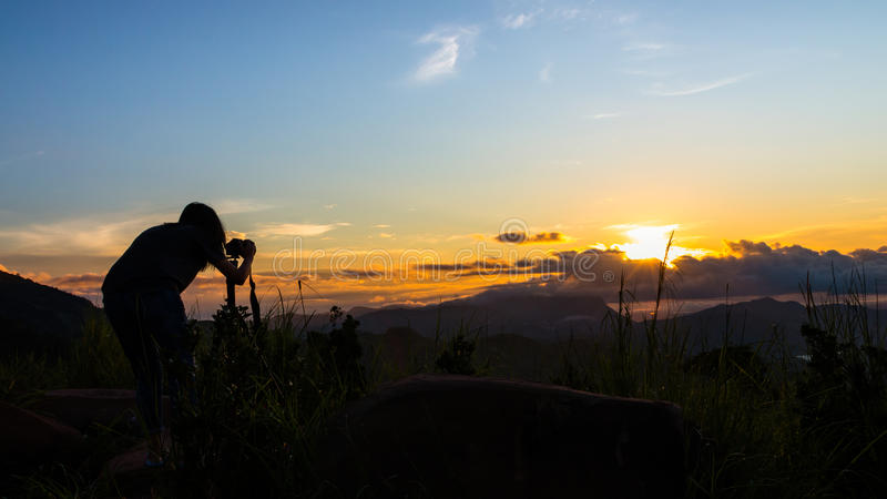 妇女摄影师和美好的日出 免版税图库摄影