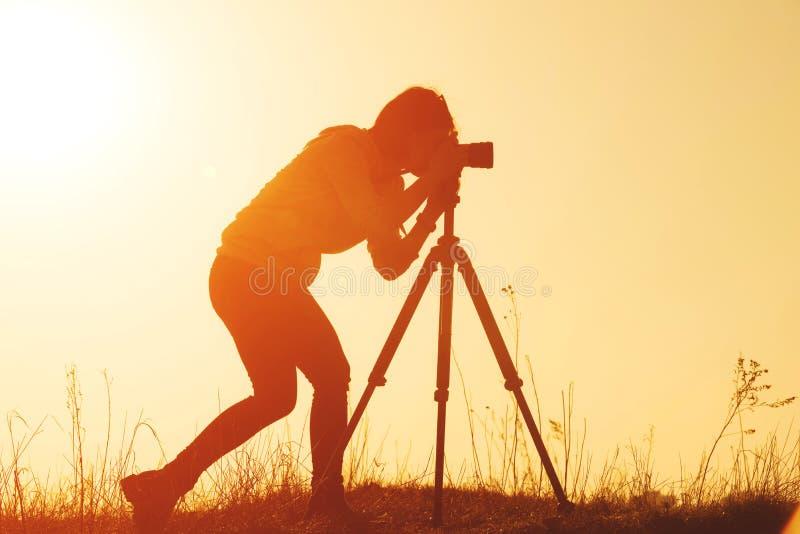 妇女摄影师在日落的射击风景剪影  库存图片
