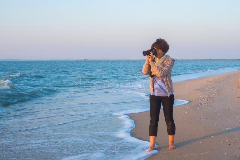 妇女摄影师拍在海滨的一张照片 免版税库存照片