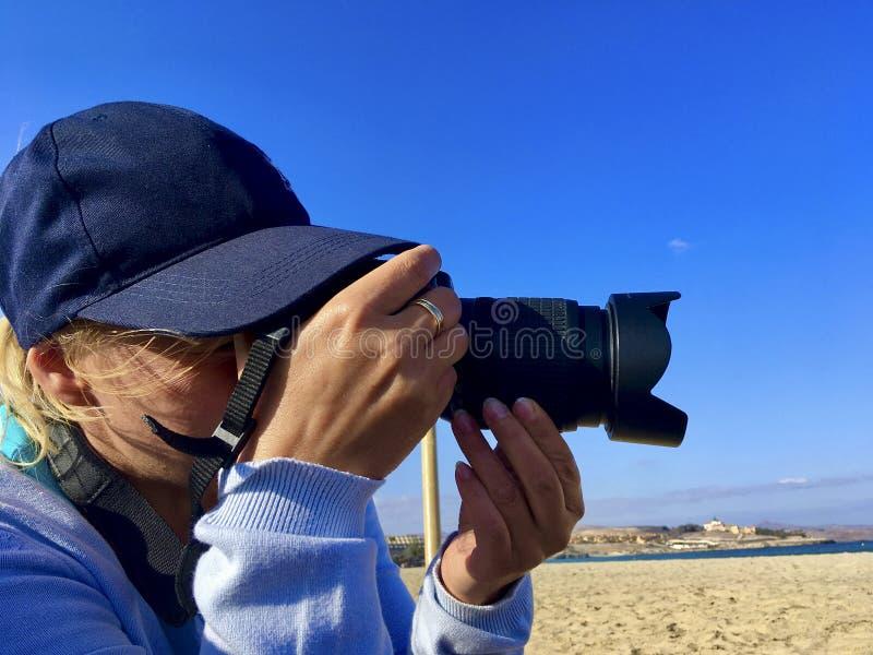 妇女摄影师拍在海滩的一张照片 免版税库存图片