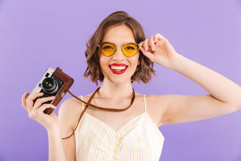 妇女摄影师摆在被隔绝在拿着照相机的紫色墙壁背景 免版税图库摄影