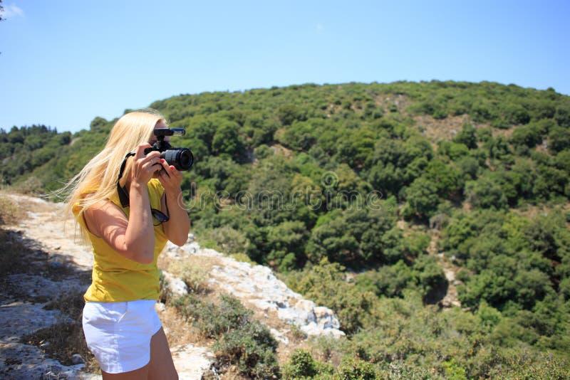 妇女摄影师自然在山的摄影师射击 汽车城市概念都伯林映射小的旅行 免版税库存照片