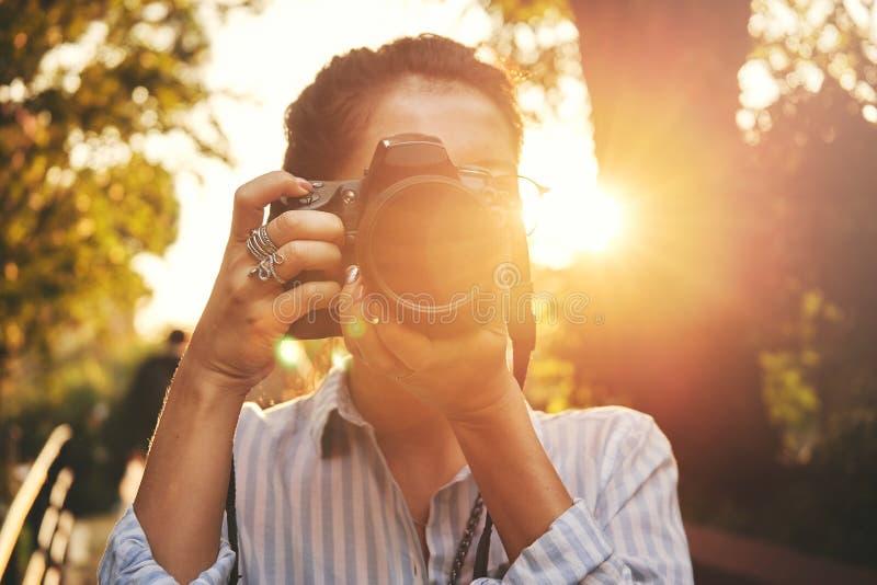 妇女摄影师,为风景照相在日落 免版税库存照片