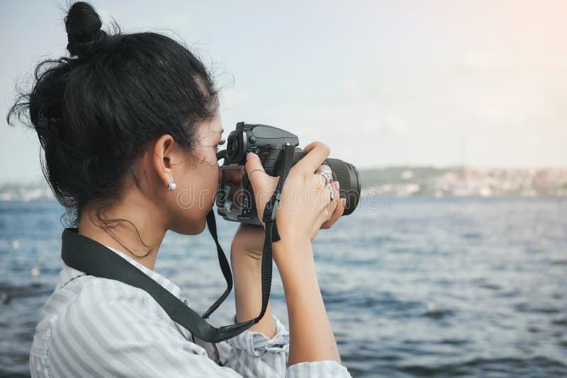 妇女摄影师,为风景照相海上 免版税库存图片