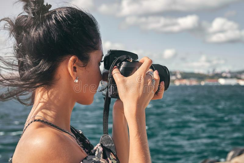 妇女摄影师,为风景照相海上 库存图片