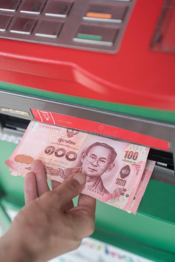 妇女撤出从ATM的现金 免版税库存图片